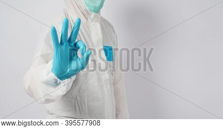 Male In Ppe Suite And Face Mask Doing Ok Hand Sign On White Background.