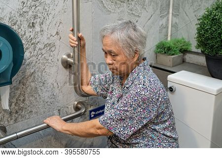 Asian Senior Or Elderly Old Lady Woman Patient Use Toilet Bathroom Handle Security In Nursing Hospit