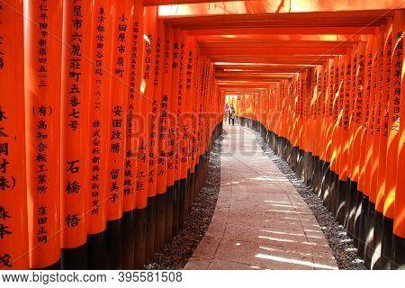 Kyoto, Japan - April 18, 2012: People Walk Under Tori Gates In Fushimi-inari Taisha Shrine Torii Gat