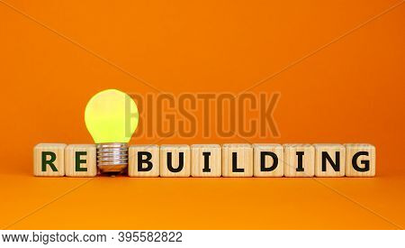 Wooden Cubes With Word 'rebuilding'. Yellow Light Bulb. Beautiful Orange Background. Business Concep