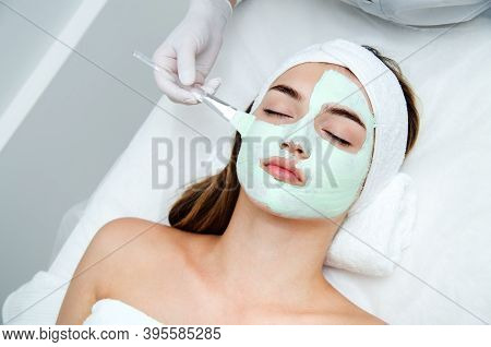 Beautiful Young Woman With Facial Mask In Beauty Salon. Girl Getting Beauty Treatment Facial Care By
