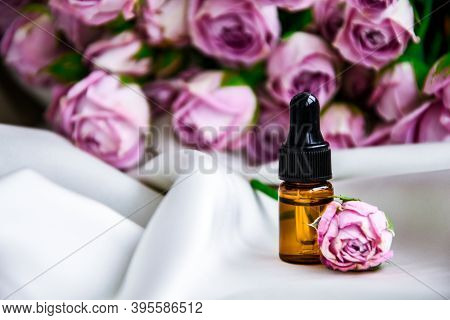 Rose Oil. Spa And Aromatherapy Rose Flowers Essential Oil Bottle With Pipette On Satin Champagne Col