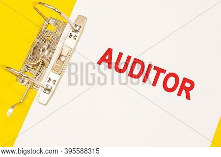 The Word Auditor On A White Background With A Yellow Folder. Business Concept