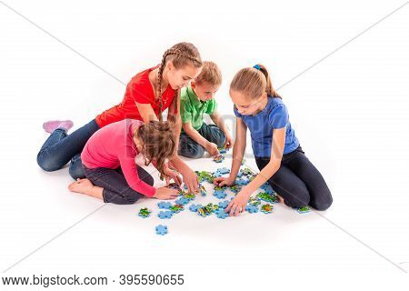 Kids Of Different Age Solving Jigsaw Puzzle Together