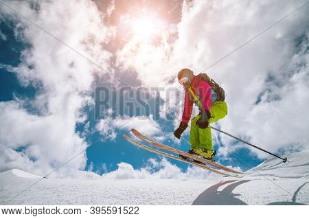 Freerider Woman In Flight After Jumping Out Of Snow On The Background Of Clouds And Winter Sun