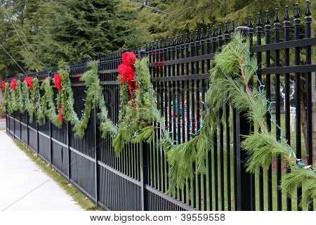 Green boughs draped on wrought iron fence