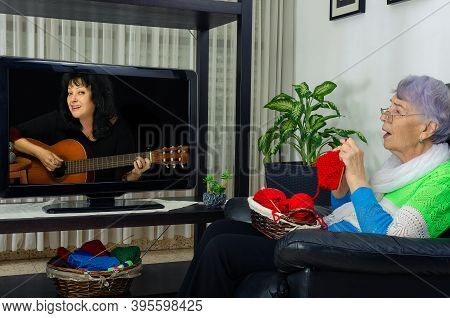 A Senior Adult Woman Loves Knitting And Watching Retro Music Channel On Tv And Singing Along To Her