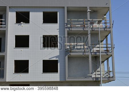 Part Of An Apartment Building Under Construction Window Openings And Unfinished Balconies On A Summe