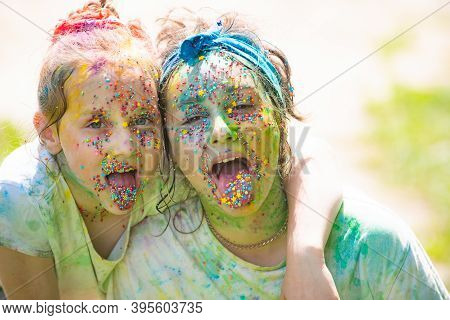 Funny Girls Showing Her Tongue Painted In Bright Colors. Cheerful Kids Faces Painted In Bright Color