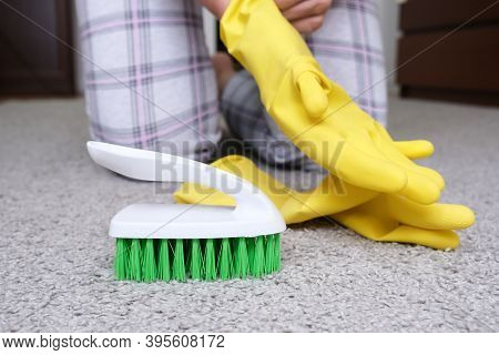 Woman In Yellow Gloves With A Green Brush Cleaning And Brushing Carpet, Removing Stains And Wool Fro
