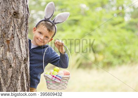 Happy Child Looks Out Of A Tree Holding Basket Full Of Colorful Easter Eggs After Egg Hunt At Spring