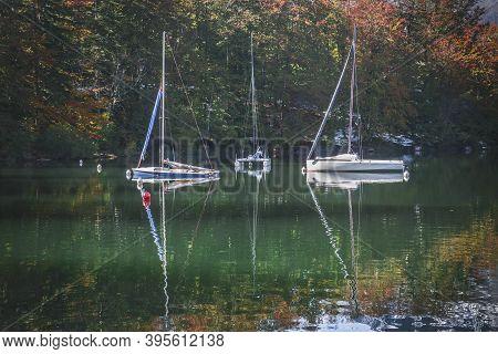 Three Yachts On Lake Bohinj In Autumn Forestin In Slovenia