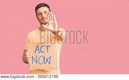 Handsome young man with bear holding act now banner with open hand doing stop sign with serious and confident expression, defense gesture