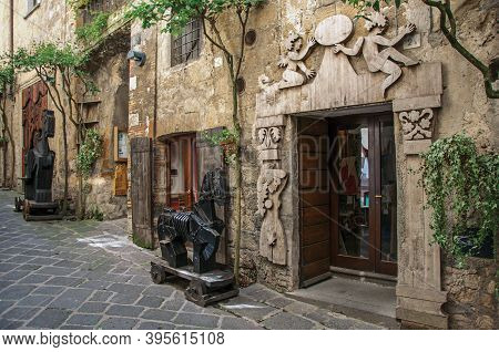 Orvieto, Italy - May 17, 2013. Overview Of A Narrow Alleyway With Old Buildings And Wooden Sculpture