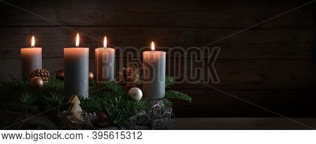 Four Burning Candles On An Advent Wreath From Fir Branches With Christmas Decoration Against A Dark