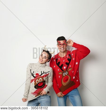 Couple In Christmas Sweaters, Deer Headband And Party Glasses On White Background