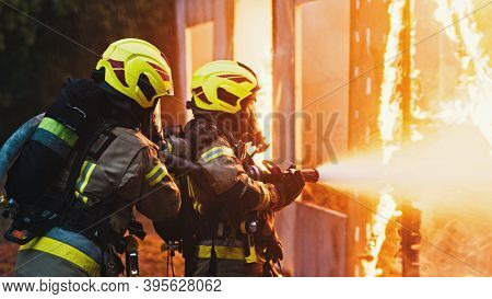 Fireman Extinguish Fire With The Hose. Burning House Fire Drill. High Quality Photo