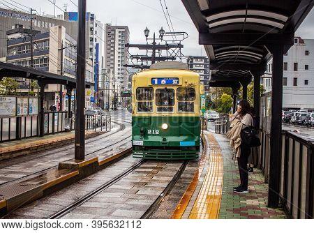 Nagasaki, Japan - 2 November 2020: Green And Yellow Tram On A Rainy Day In Nagasaki