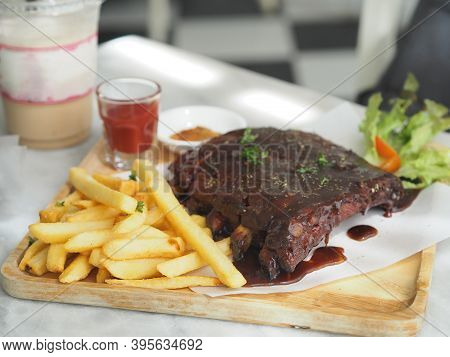 Pork Spareribs Bbq, Barbeque Pork Ribs With French Fries Vegetable Salad, Tomato Sauce In A Clear Gl