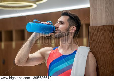 Young Man In Bright Tshirt Feeling Thirsty After Workout