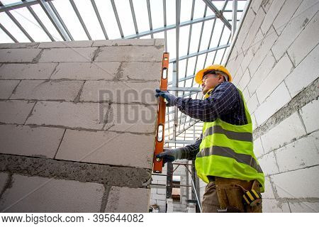 Asain Worker Using Water Level Meter Measuring The Wall Builder Working With Autoclaved Aerated Conc