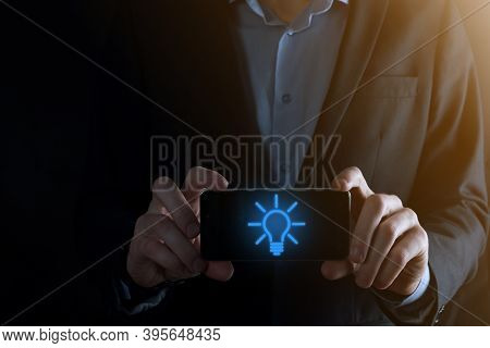 Businessman In A Suit Hold Smartphone With A Light Bulb In His Hands. Holds A Glowing Idea Icon In H