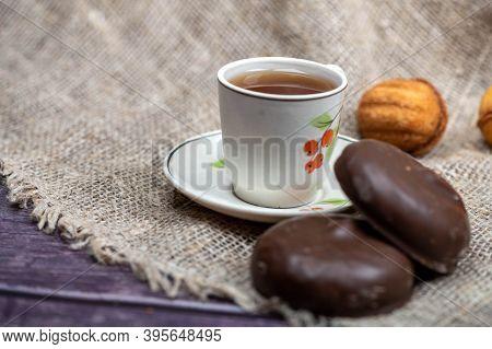 A Small Mug Of Tea, Chocolate Cake And Homemade Cookies On A Background Of Coarse Homespun Fabric. C