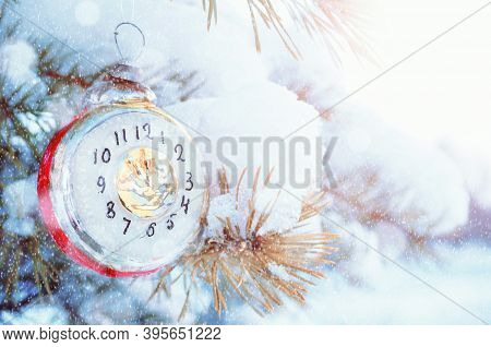 New Year 2021 background, New Year glass Christmas toy in the form of clock showing the New Year Eve, on snowy fir tree branch. New Year 2021 card.