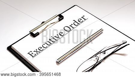 Executive Order Text Written On Paper With Pen And Glasses