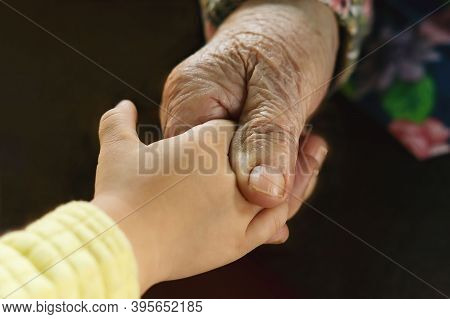 A Great-grandmother Holds The Hand Of Her Little Great-granddaughter. An Elderly Woman Holds The Han