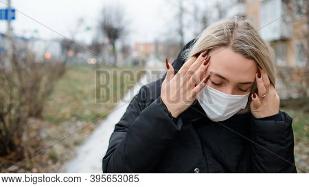 Young Woman In A Medical Face Mask Outside. Girl Holding Her Head. Concept Of Headache, Depression,