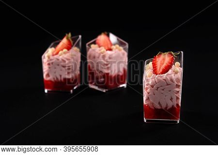 Closeup Of Three Glasses Filled With Whipped Pink Cream And Red Jam Decorated With Fresh Berries And