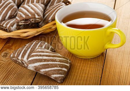 Wicker Basket With Gingerbread, Few Striped Gingerbreads, Yellow Glass Cup With Tea On Wooden Table