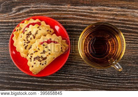 Shortbread Cookies With Raspberry Jam And Linseeds In Red Saucer, Transparent Cup With Tea On Dark W