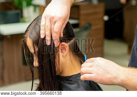 Hands Of A Hairdresser Combing The Hair Of A Young Woman Parted In Sections At The Barbershop