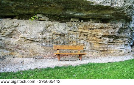 Huge Geological Layered Rock From Two-way Pressures With Wind Erosion Behind A Bench And Meadow