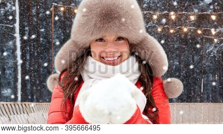 christmas, season and holidays concept - happy woman in winter fur hat holding snow in her hands over outdoor ice skating rink on background