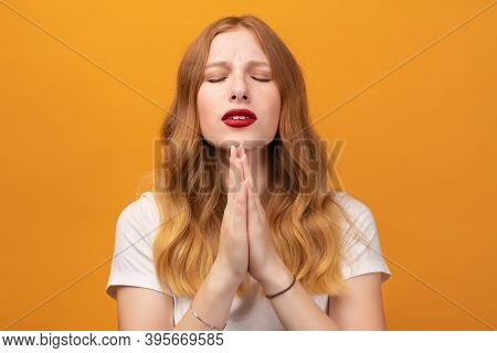 Pretty Girl With Wavy Redhead, Wearing White T-shirt Holding Palms Together. She Meditating, Praying