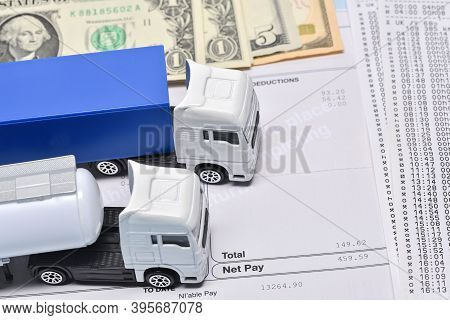 A Lorry Toys, Payroll With Dollar Bill And Face Mask In Concept About Transport Departament Against