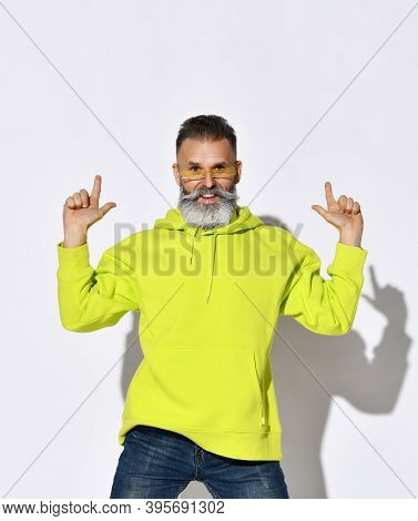 Stylish Bearded Middle Aged Man Hipster In Yellow Glasses, Hoodie And Blue Jeans Dances With Fingers