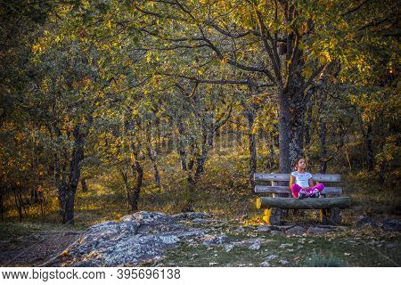 Child Girl Sitting In The Middle Of The Forest. Natural Reserve Garganta De Los Infiernos, Extremadu