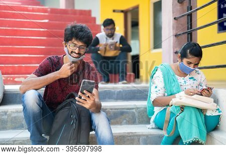 College Students Busy Using Mobile With Face Mask - Happy Millennial Friends At University Campus Ha