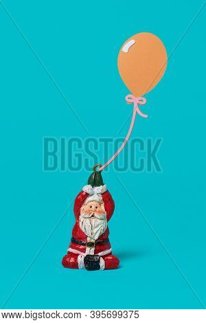 a figurine of santa claus holding a paper cutout in the shape of a balloon on a blue background