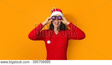 Young Girl In Santa Claus Hat On Bright Color Background Looking Through Binoculars. New Year And Ch