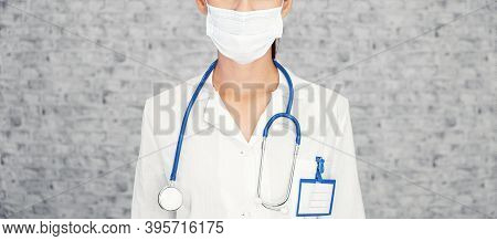 Doctor Woman Stands On Background Of Brick Wall Concept To Stop Coronavirus. Girl Doctor Wearing Pro