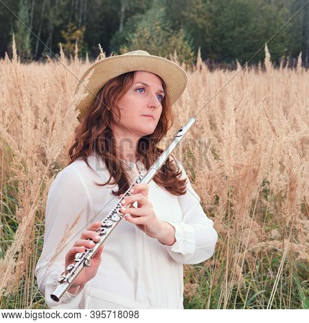 A Flute Player Holds A Concert Flute While Standing In The Tall Autumn Grass. A Musician With A Wind