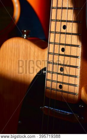 Electric Guitar Background. Maple Fretboard And Swamp Ash Body Close-up.