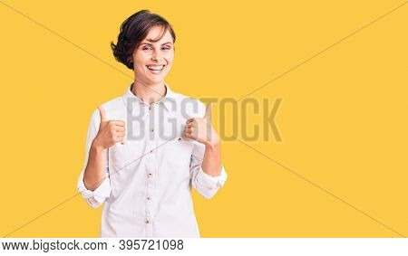 Beautiful young woman with short hair wearing elegant white shirt success sign doing positive gesture with hand, thumbs up smiling and happy. cheerful expression and winner gesture.