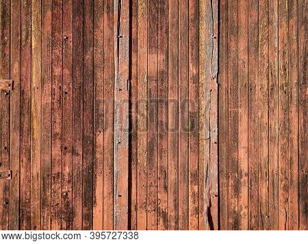 rustic wooden background of a barn wall - planks of weathered pine red painted wood with  knots, holes and nails