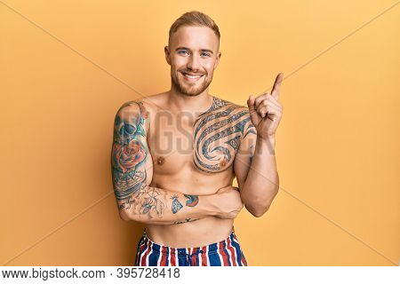 Young caucasian man wearing swimwear shirtless with a big smile on face, pointing with hand and finger to the side looking at the camera.